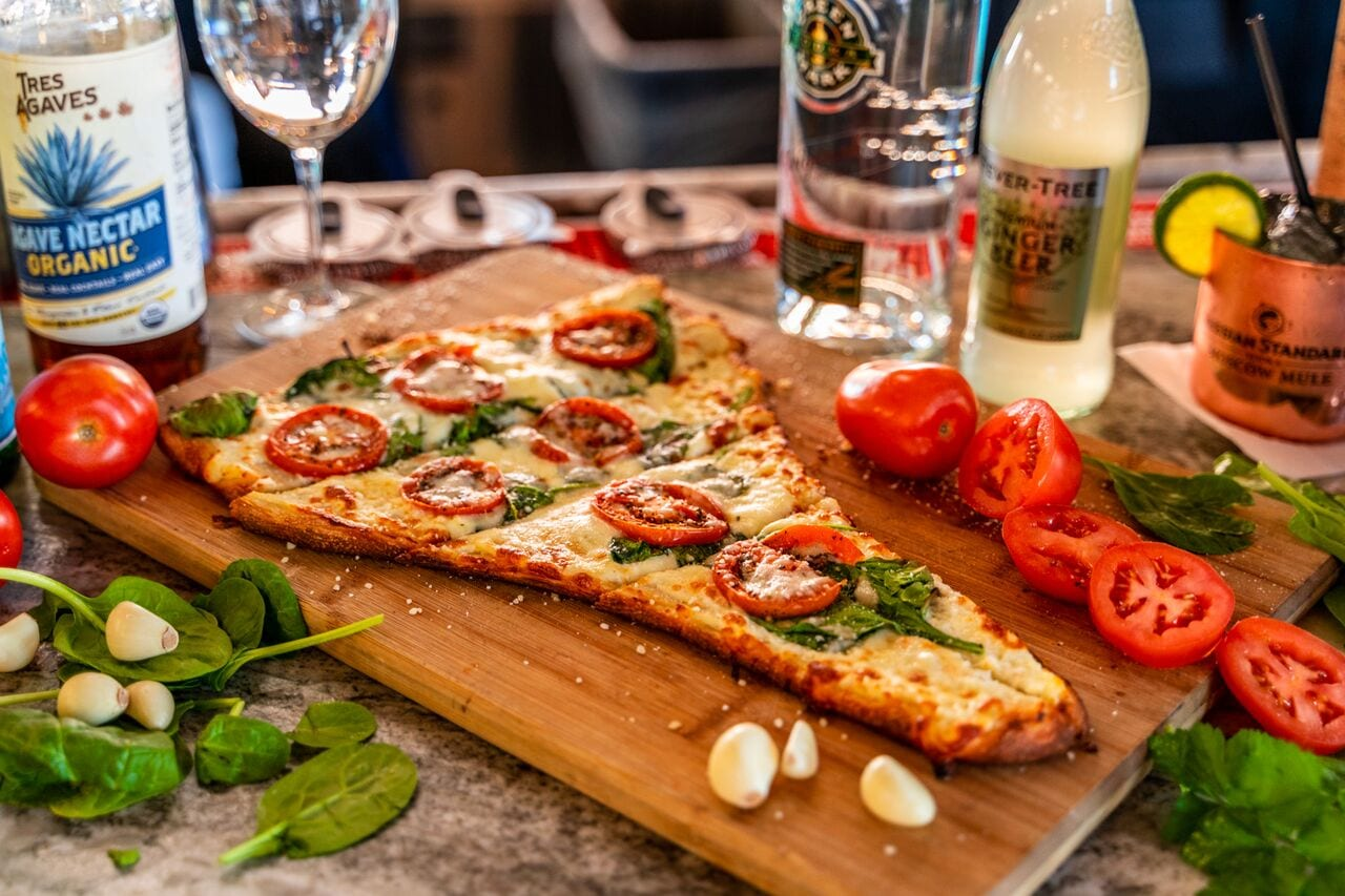 Rustica slice of pizza with tomatoes cheese and basil