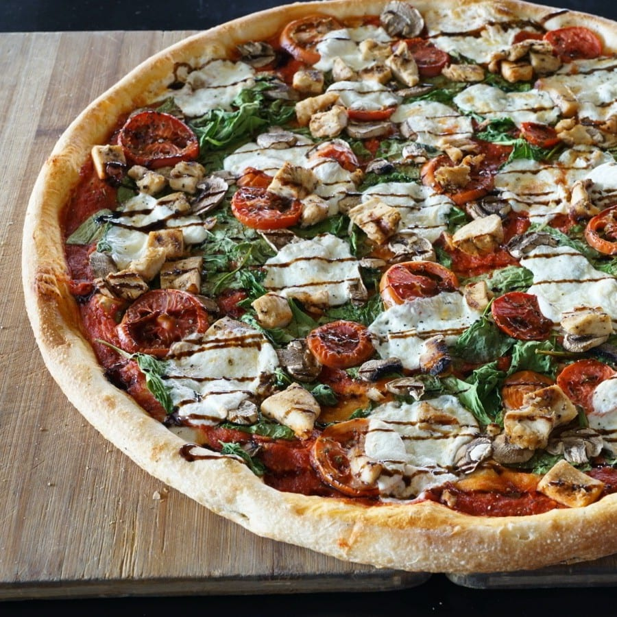 whole pizza topped with mozarella, tomato, and basil