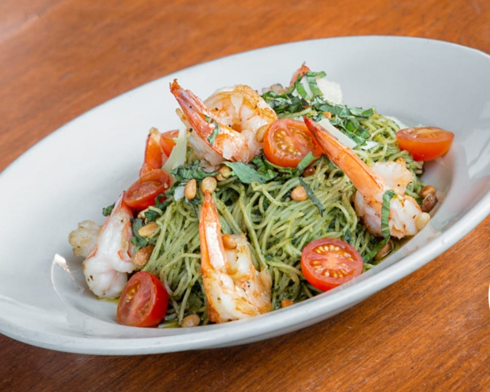 angel hair pasta with pesto sauce topped with shrimp