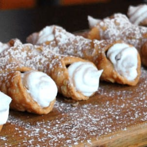 Line of conollis filed with cream and topped with powdered sugar